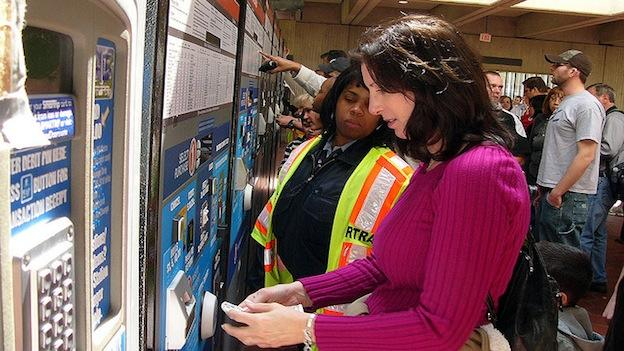 A Metro transit employee helps a rider purchase a fare card.