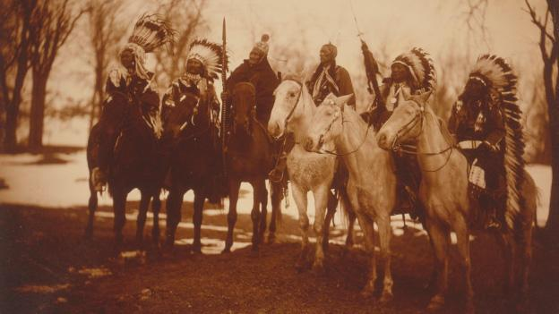All six chiefs who attended President Teddy Roosevelt's 1905 inaugural parade line-up in full regalia prior to the event. From left to right: Little Plume (Piegan Blackfoot); Buckskin Charley (Ute); Geronimo (Chiricahua Apache); Quanah Parker (Comanche); Hollow Horn Bear (Brule Sioux); and American Horse (Oglala Sioux).
