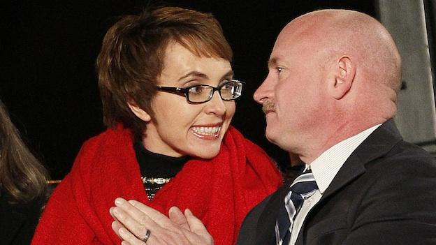 Rep. Gabrielle Giffords, left, and her husband, former astronaut Mark Kelly, sit together at the start of a memorial vigil remembering the victims and survivors one year after the Arizona congresswoman was wounded in a shooting that killed six.