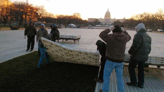 A crew lifts the protective barrier put down to shield the lawn on the National Mall during inauguration.