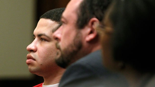 Eric Rivera Jr., 23, left, convicted in the 2007 killing of Washington Redskins NFL football player Sean Taylor, listens as Miami-Dade Circuit Judge Dennis Murphy imposes a 57-year prison sentence on Thursday, Jan. 23, 2014, in Miami. Rivera Jr.'s attorneys, Chris Brown, center, and Janese Caruthers, are seated with him.