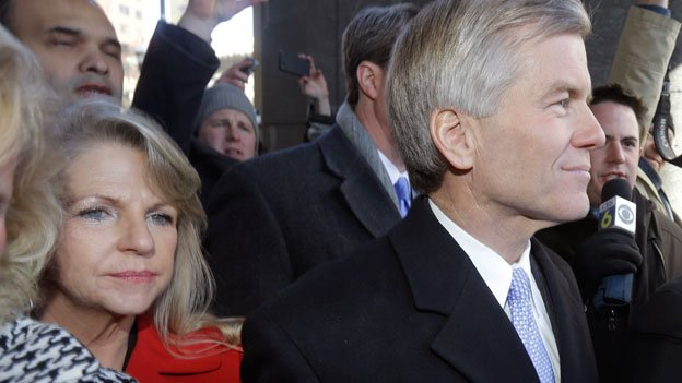 Former Virginia Gov. Bob McDonnell, right, and his wife, Maureen, left, are surrounded by family and supporters as they leave Federal court in Richmond, Va., Friday, Jan. 24, 2014. McDonnell and his wife pleaded not guilty Friday to federal charges that they traded their influence for tens of thousands of dollars in gifts and loans, and both will be allowed to remain free until their trial.