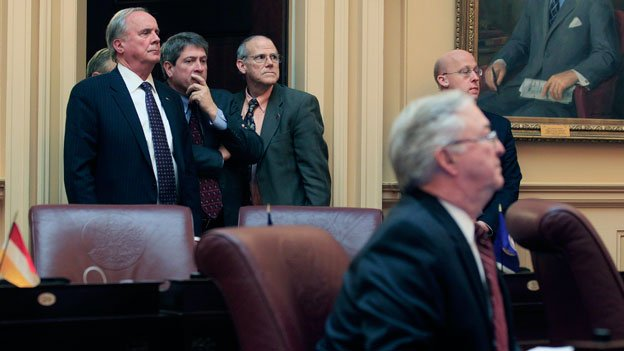 State Senators John Watkins, R-Powhatan, top left, Stephen Martin, R-Chesterfield, top center, and Frank Ruff, R-Mecklenburg, watch the vote on the new president pro tem during the Senate session at the Capitol in Richmond, Va., Tuesday, Jan. 28, 2014. Most of the Republican Senators left their seats for the vote.