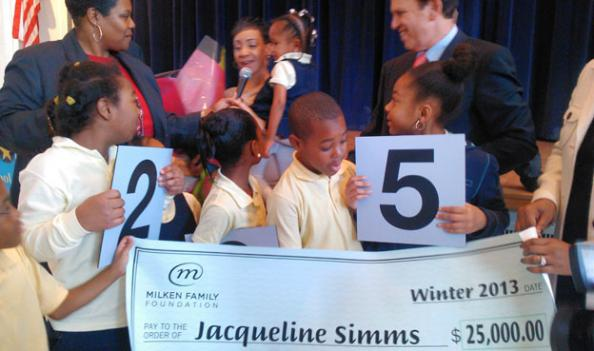 Students and other teachers gather around Jacqueline Simms (center, holding child) as she accepts the Milken Educator Award.