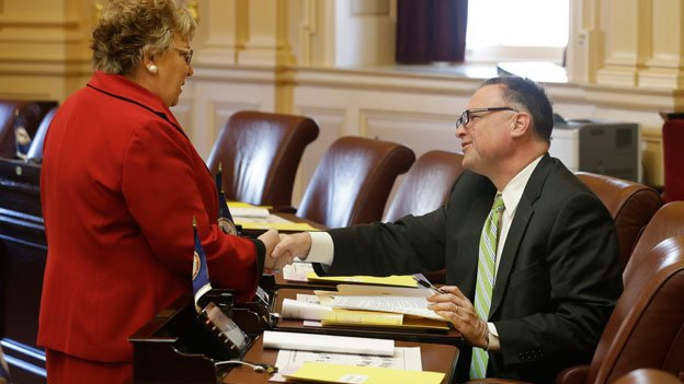 Virginia State Sen. Creigh Deeds, D-Bath, right, is greeted by Senate Clerk Susan Schaar, left, prior to the opening ceremonies of the 2014 General Assembly at the Capitol in Richmond, Va., Wednesday, Jan. 8, 2014. Deeds face bears the wounds suffered during a domestic altercation with his son.