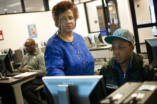 Part-time librarian Janet Sims-Wood, 67, helps student Andre Williams navigate the online catalogue at the Accokeek Library at Prince George's Community College in Largo, Md.