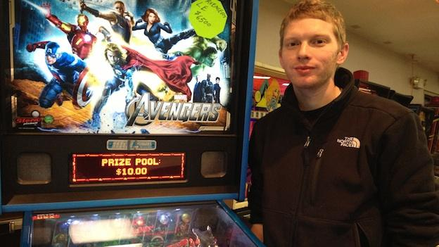 David Horner, one of the organizers of the Fairfax Pinball Open, stands in front of the new Avengers pinball machine.