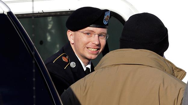 Army Pfc. Bradley Manning, center, steps out of a security vehicle as he is escorted into a courthouse in Fort Meade, Md.
