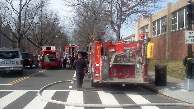 D.C. Fire and EMS crowded on the corner of 4th and I Streets, SW, across from Amidon-Bowen Elementary, after an envelope containing white powder was reported.