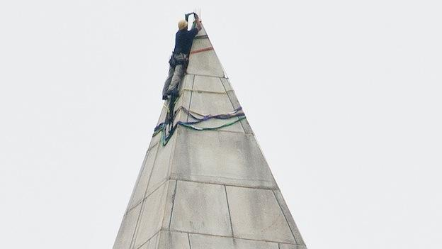 Rigging is looped over the tip of the Washington Monument on Tuesday Sept. 27, 2011. The rigging will be used by a four-person that will rappel down the four sides of the monument and help document damage from the earthquake.