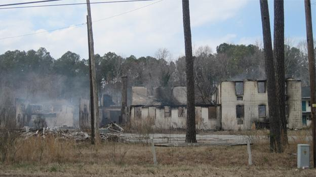 The Whispering Pines Motel smolders after being razed by an arsonist.