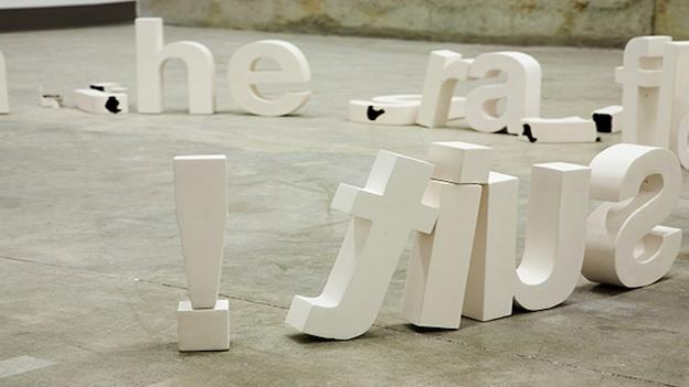 "In Nothing Rhymes With Orange, Thomas Müller arranges ceramic letterform sculptures into words and phrases, including ""the man in the gray flannel suit has fallen over!"""