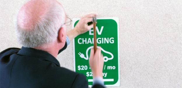 Bob Bruninga installs one of his EV Charging signs.