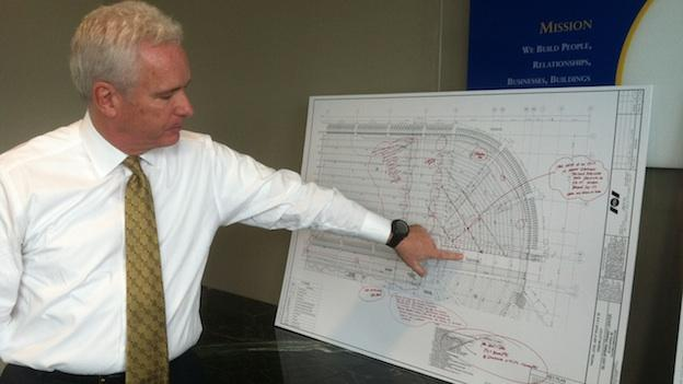 Foulger Pratt Executive Bryant Foulger pointing to construction plans for the Silver Spring Transit Center.