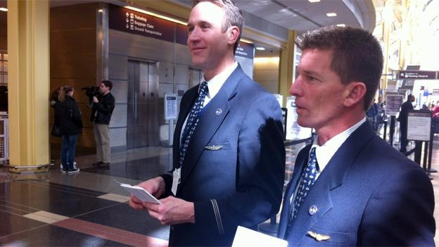 Flight attendants Robert Valenta, left, and Tim Weston hand out fliers on the knife ban issue.