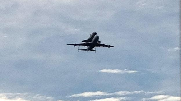 Hitching a ride on top a special NASA Boeing 747 jet, the space shuttle Discovery soars past Capitol Hill in Washington, after a flight from Cape Canaveral, Fla., Tuesday, April 17.