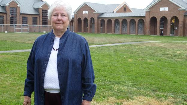 Life-long Lorton resident Irma Clifton stands in the courtyard at the Workhouse Arts Center, which was once Lorton prison.