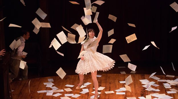 Emily Young (Sylvia) showers the stage with letters in The Two Gentlemen of Verona at the Folger Theatre.