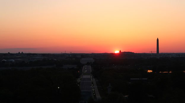 The sun rises above D.C., as photographers capture the moment from the Arlington National Cemetery.