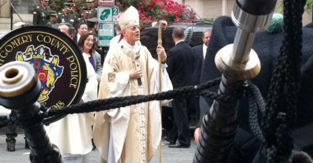 Cardinal Wuerl leads the 'Blue Mass' procession to St. Patrick's Catholic Church, with a bagpipe in the foreground.