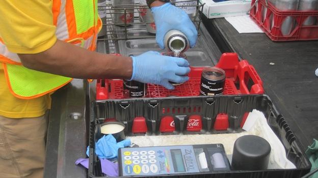 An inspector at a Montgomery County gas station pours gas into the glasses for testing.