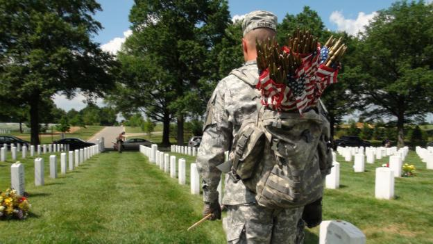 A member of the 3rd Infantry Division places flags on markers at Arlington National Cemetery.