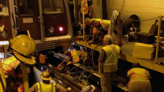 First responders work to free the employee, who was pinned under a Metro train.