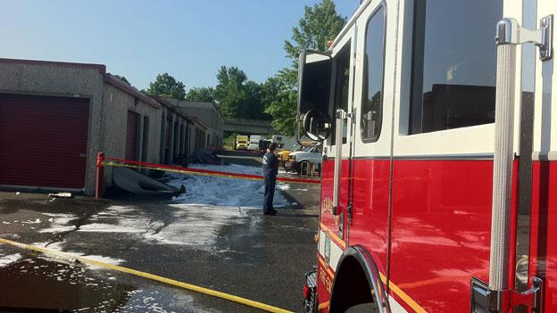 Firefigthers clean up[ the scene after extinguising a fire in a self-storage unit in Alexandria.