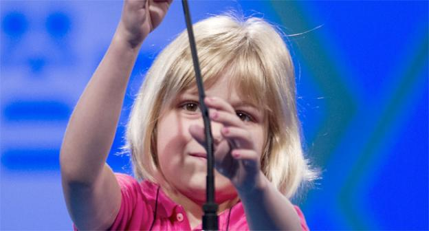 Lori Anne Madison, 6, of Woodbridge, Va., the youngest speller in the National Spelling Bee, adjusts the microphone to spell her word.