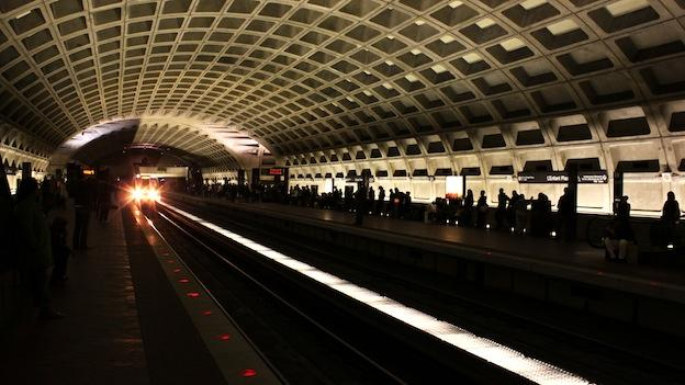 Passengers wait on the L'Enfant Plaza Metro platform for the next train.
