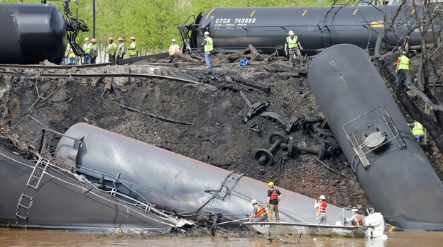 Survey crews in boats look over tanker cars as workers remove damaged tanker cars along the tracks where several CSX tanker cars carrying crude oil derailed and caught fire along the James River near downtown Lynchburg, Va., Thursday, May 1, 2014. Virginia state officials were still trying Thursday to determine the environmental impact of the train derailment.