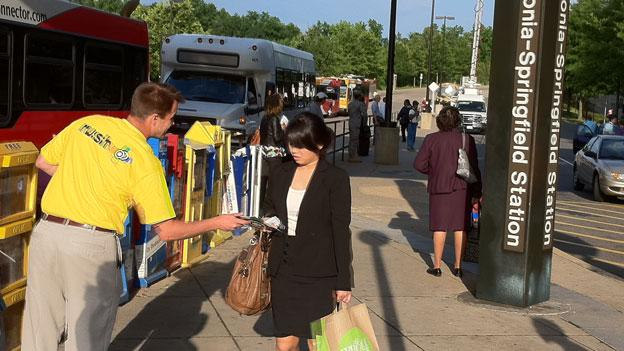 "A Metro employee hands out information about the new ""Rush Plus"" service at the Franconia-Springfield Metro station."