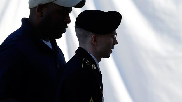 Army Pfc. Bradley Manning, center, is escorted into a courthouse in Fort Meade, Md.