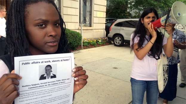 Lucy Mwaka stands outside the Kenyan embassy holding a flier accusing a diplomat of slavery.