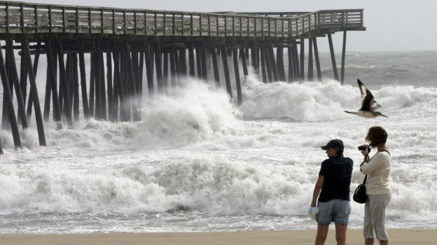 Rough surf pounds a fishing pier as Tropical Storm Hanna passes through Virginia Beach, Va., in 2008. Virginia is dependent on coal mining but it also faces routine flooding from rising sea levels.