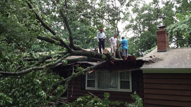 A huge tree fell over the roof of a house in Sterling, Va., after a fast moving storm pummeled through the Washington, D.C. area on Thursday, June 13, 2013.