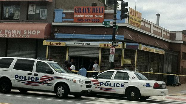 Police investigate the scene at Grace Deli on H Street NE, where deli owner June Lim was found dead early this morning.