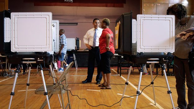 Maryland Democratic gubernatorial candidate, Lt. Gov. Anthony Brown, left, talks with volunteer Alice Toliver at a polling place inside Hazelwood Elementary/Middle School on primary day in Baltimore on Tuesday, June 24, 2014.