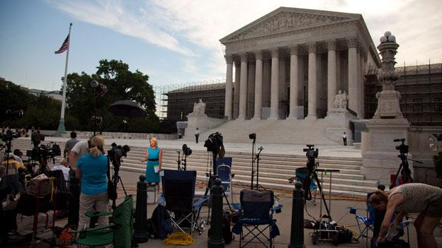 Journalist wait outside the Supreme Court in Washington June 25.