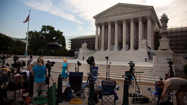 Journalist wait outside the Supreme Court in Washington June 25.