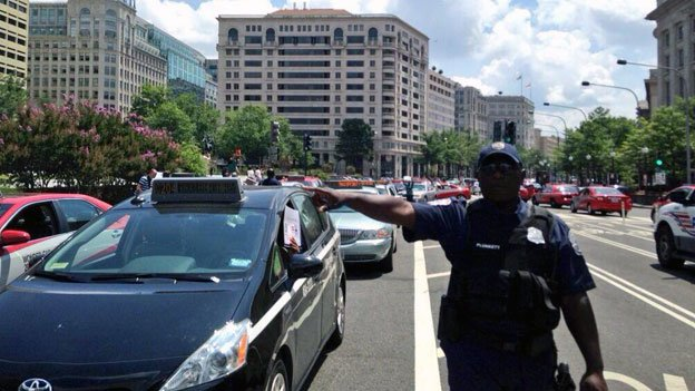 A police officer surrounded by D.C. taxicabs tries to deal with gridlock outside of the Wilson Building.