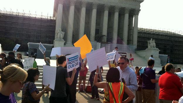 Activists gathered on the steps of the Supreme Court to hear their ruling on the Affordable Care Act Thursday, June 28.