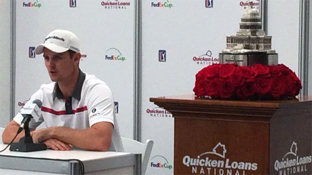 Justin Rose sits next to the Quicken Loans trophy, which he won for the second time this weekend.