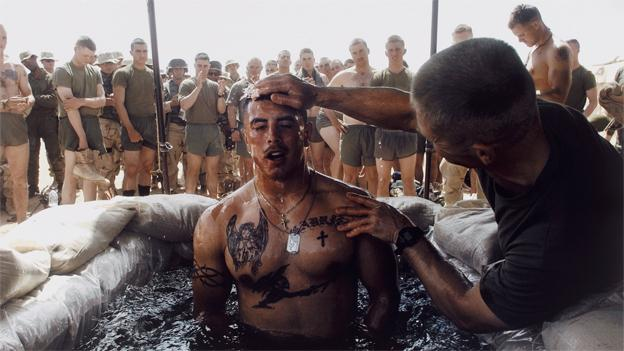 Navy Chaplain Lt. Commander Tom Webber baptizes Corporal Albert Martinez in a sandbag lined pool during a ceremony at Camp Inchon, Kuwait, March 16, 2003.