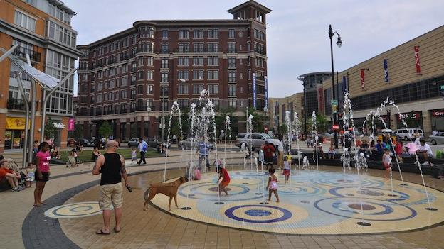 Children and adults play the near water fountain in Columbia Heights.