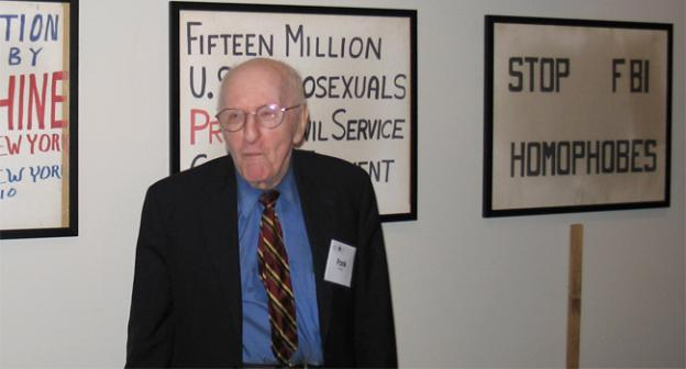 The late Frank Kameny standing in front of several protest signs.