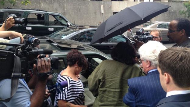 Former Gray associate Jeanne Harris, center, in green, makes her way to a vehicle amid a throng of observers and reporters after pleading guilty Tuesday to fraud, conspiracy and campaign finance contributions.
