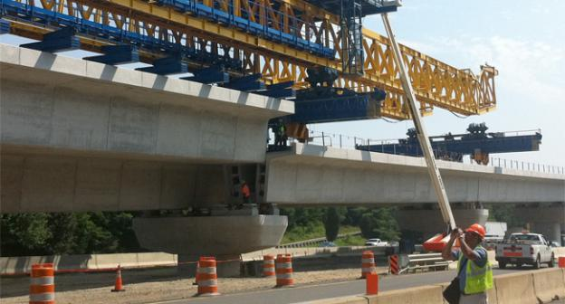 Workers use a truss to lower the 380-tons of concrete span into place.