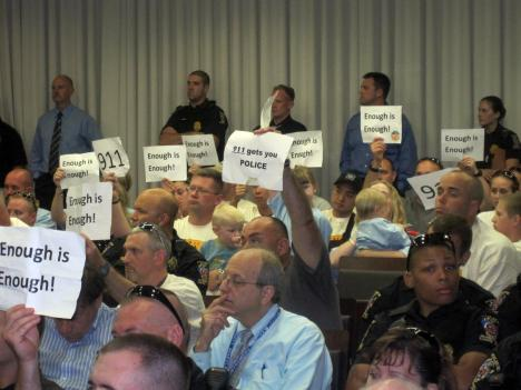 In this July 2011 file photo, Montgomery County police officers hold up signs during the Montgomery County Council's vote on the bill that removed effects bargaining from their collective bargaining agreement. That bill will come up for countywide referendum in November.