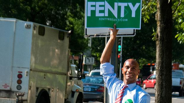 Former Mayor Adrian Fenty waving a campaign sign in Northwest Washington, D.C., during his 2010 re-election campaign.